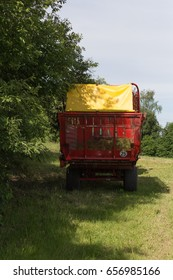 on a sunny day in june in south germany in rural countryside you see machine, wheels and parts of farmhouse equipment for harvesting and agricultural work