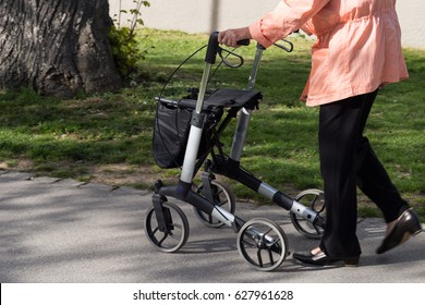 on a sunny day in spring seniority lady walks with rollator in park in south germany
