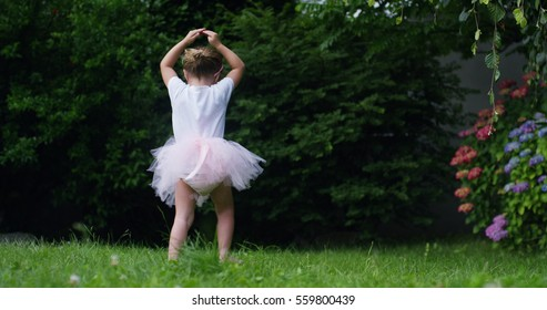On a sunny spring day a baby girl dressed as a ballerina plays tries to stand up and to take its first steps alone without a mother