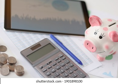 On table is calculator pig and tablet with coins. Advantageous offers on deposits concept