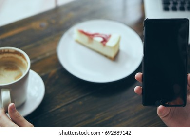 On the table cheesecake, coffee mug, laptop, phone