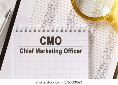 On the table are financial reports, a pen, a magnifying glass and a notebook with the inscription - CMO. Chief Marketing Officer. Business and finance concept.