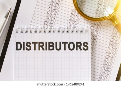 On the table are financial reports, a pen, a magnifying glass and a notebook with the inscription - DISTRIBUTORS. Business and finance concept.