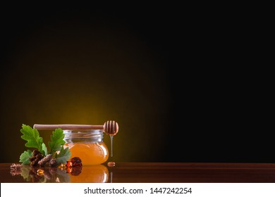 On the table is a glass jar with honey on a dark background. Honey drips from a wooden spoon. Near the banks lie stones of amber, a branch of an oak tree, pine buds, and a root of a calgan.