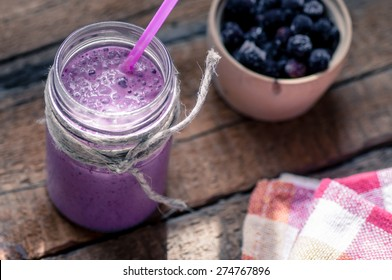 On the table with a glass of smoothies and berries. Rustic style