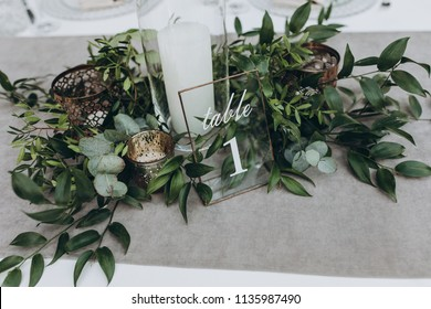 on table with gray tablecloth is a candle in candlestick, plate with number and composition of greenery