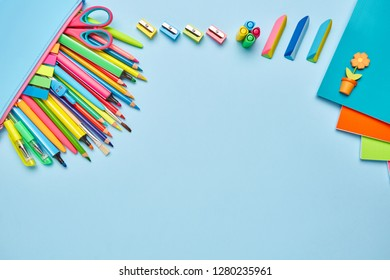 On the table laid composition from school stationery. Working place elements. Group of school supplies on table. Top view, flat lay.