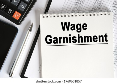 On the table lies a smartphone, a calculator and a notebook with the inscription- Wage Garnishment. Business concept