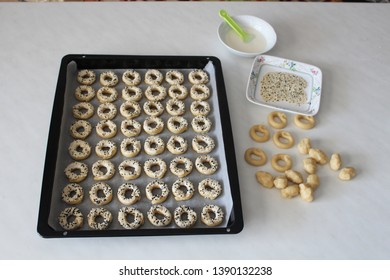 On the table, lined up on the baking sheet. ready to cook. salty, white sesame, black seed cookies. and doughs under construction. plate, bowl, brush. Ramadan, iftar, sahur