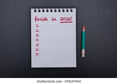 On the table is a notebook with the words: finish in 2016