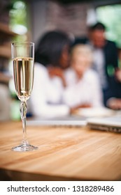 On the table in the office is a glass of champagne. Business partners celebrate successful negotiations. Close-up shot