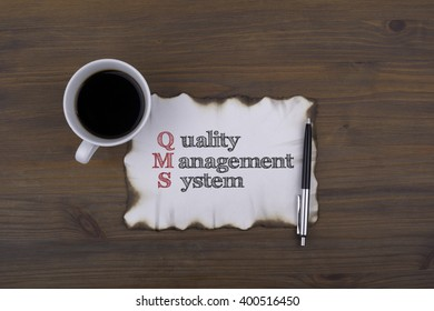 On the table a piece of paper and text. QMS concept: quality management system