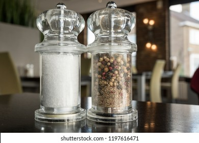 on the table in the restaurant there are pepper and salt mill