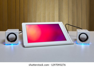On the table is a tablet computer mounted on a tablet PC holder and connected to a two small white speaker with LED lighting.