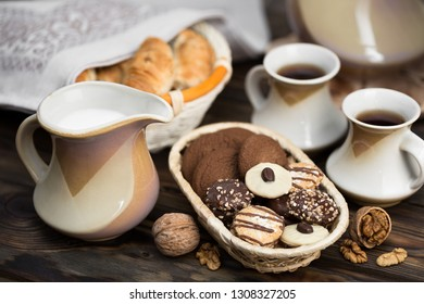 On the table: two cups of tea, milkman and cookies in chocolate glaze sprinkled with caramel crumbs and crushed nuts in a wicker dish.