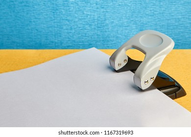 On the table is a white sheet of paper and a puncher.