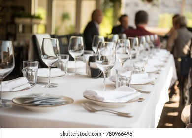 On the table is a white tablecloth, glasses, cutlery. In the background, a group of people full of blurring have a lunch
