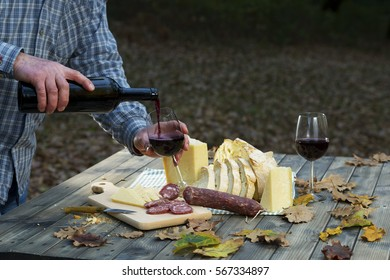 On the table in the wood pours drink the wine in the glass. / Traditional Dinner of Sardinia