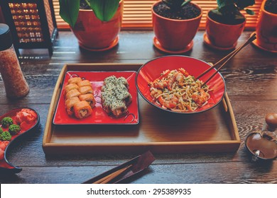 On the table is a wooden dressing on it two red plates with Japanese noodles with shrimp and sushi. Lunch in the office Sushi and Japanese rice noodles to order