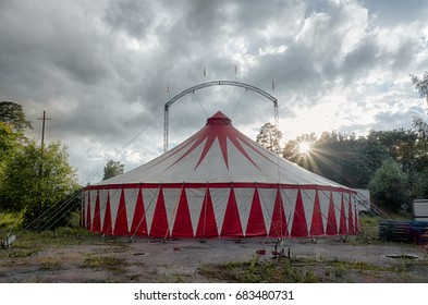 On the territory surrounded by trees, a mobile circus tent is installed.