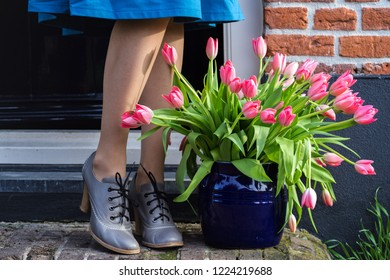 on the threshold of the house a vase with pink tulips and female legs in heels. The Netherlands