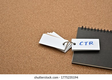 On top of the notebook on the corkboard is a wordbook with the word CTR written on it. It means Click Through Rate.