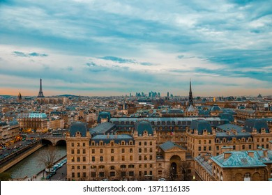 On the top of Notre Dame Cathedral in Paris, France, cloudy blue and yellow sky