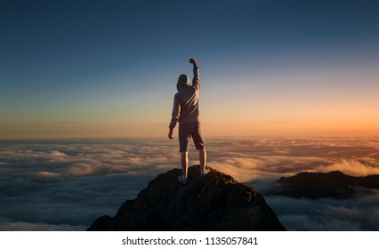 On top of the world. Man standing on the mountain above the clouds.