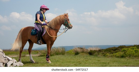 On top of the world-young woman and her pony riding the remote hilly bridleways of Shropshire, England