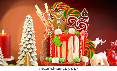 On trend candyland Christmas drip cake with Christmas lights bokeh background.