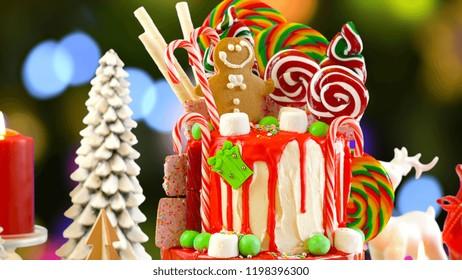 On trend festive candyland Christmas drip cake against festive Christmas tree bokeh lights background.