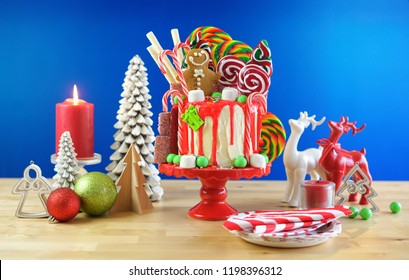 On trend festive candyland Christmas drip cake on blue background.