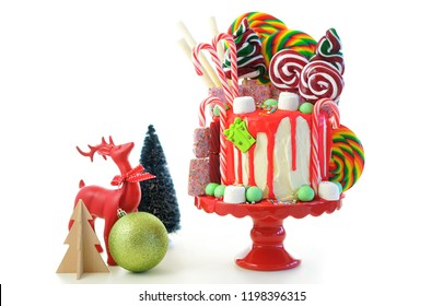 On trend festive candyland Christmas drip cake on white background.
