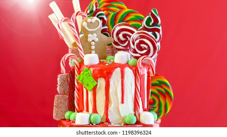 On trend festive candyland Christmas drip cake on red background.