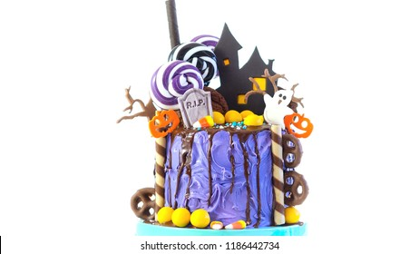 On trend Halloween candyland fantasy novelty drip cake on white background.
