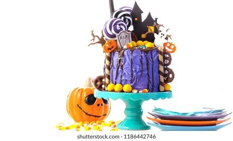 On trend Halloween candyland fantasy novelty drip cake on white background.