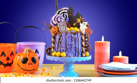 On trend Halloween candyland fantasy novelty drip cake in purple theme colorful party table setting.
