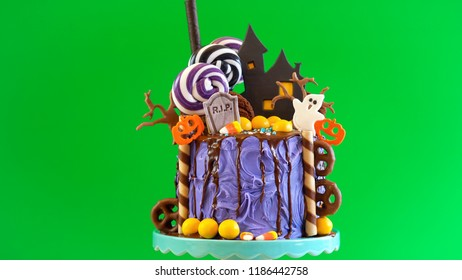 On trend Halloween candyland fantasy novelty drip cake and party table against chroma key green background.