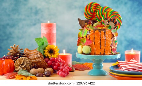 On trend Thanksgiving candyland novelty drip cake with colorful Fall leaves and cornucopia table setting.