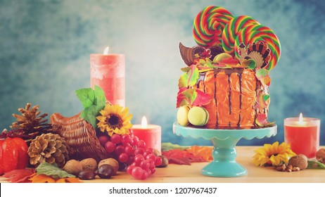 On trend Thanksgiving candyland novelty drip cake with colorful Fall leaves and cornucopia table setting with retro filter.