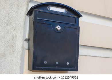 On the wall of the house is a black box for receiving letters, newspapers, correspondence. At the corners different numbers are fixed. Mailing address, receiving news.