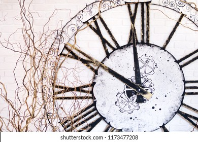 On the wall a large clock with Roman numerals showing at ten minutes to twelve