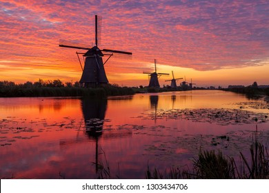 on the water there are several windmills in Kinderdijk in Holland by sunrise