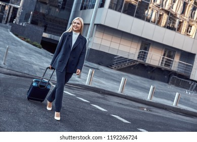 On the way to business meeting. Full length of young woman in suit pulling luggage while walking outdoors