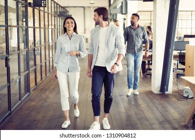 On the way to business meeting. Full length of young modern people in smart casual wear having a discussion while walking through the office