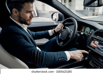On the way to business meeting. Handsome young man in full suit pushing buttons while driving a car