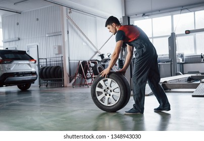 On the way to the car. Mechanic holding a tire at the repair garage. Replacement of winter and summer tires.