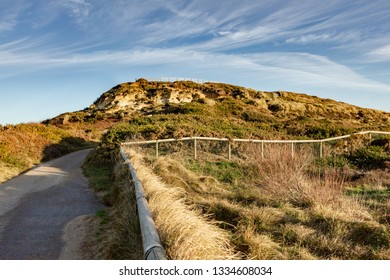 On the way of Hengistbury Head summit under a majestic blue sky and white clouds