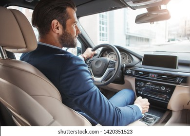 On the way to success. Confident and handsome young businessman in full suit is driving his new car and smiling.