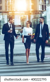 On the way to work. Full length of three smiling business people talking to each other while crossing the street